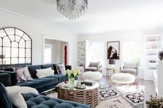 Chic living room with blue velvet sectional, gray armchairs, a large area rug, and a chandelier