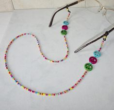 I created this eyeglass holder using turquoise, purple, and green dyed howlite peace sign beads finished with multicolored bright seed beads. Seed Bead Necklace, Seed Bead Jewelry, Cute Jewelry, Beaded Jewelry, Handmade Jewelry, Beaded Necklace, Eyeglass Holder, Bracelet Crafts, Eyeglasses