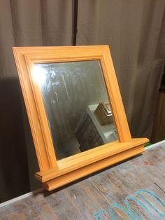 Painted and distressed mirror frame with shelf.