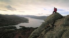 Hillwalker on summit of Ben An with view over Loch Katrine, Trossachs