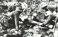 German troops trying to rescue what looks like a French soldier from sinking in a mud hole, 1918-The concentration of so much fighting in such a small area devastated the land, resulting in miserable conditions for troops on both sides. Rain combined with the constant tearing up of the ground turned the clay of the area to a wasteland of mud full of human remains. Forests were reduced to tangled piles of wood by constant artillery-fire and eventually obliterated.