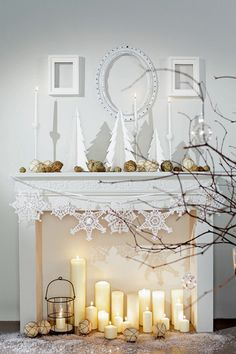 Holiday white fireplace: white candles, black wrought iron, pine cones, twigs, white porcelain figurines
