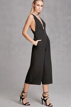 A sleeveless woven jumpsuit by Selfie Leslie™ featuring a plunging neckline, inverted pleats at the waist, wide cropped legs, side seam pockets, and a cutout back with two exposed zippers.