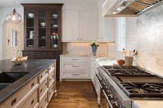 Well appointed kitchen boasts a stainless steel oven range fixed against a marble backsplash beneath a white hood and beside white shaker cabinets accented with polished nickel pulls and a gray and white marble countertop custom lit by lights mounted beneath white upper shaker upper cabinets.