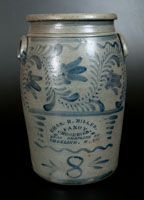 Eight-Gallon Stoneware Jar with Profuse Freehand Cobalt Decoration and Wheeling, WV Advertising, Greensboro, PA origin, circa 1875, cylindrical jar with tooled shoulder, semi-rounded rim, and applied lug handles, decorated with an unusual and large tulip vine design across the top half of the jar.