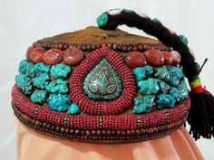 Unusual Antique Tibetan Pilgrims Cap lavishly encrusted with natural Turquoise nuggets, agate, and horn beads was handcrafted approximately 100 years ago in the Tibetan Autonomous Region (Xizang). The crown on this unique cap is made of old embroidered textile, with a swinging top-knot that is embellished with natural Turquoise and cowrie shells. When not being worn, these caps were carried by their top-knots, which often had to be replaced when they broke or wore through.: