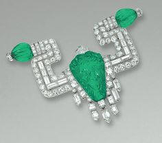 FINE EMERALD AND DIAMOND BROOCH,  CIRCA 1925.  Of mythological inspiration, the carved emerald depicting the head of Pan, suspending a fringe of collet-set baguette and shield-shaped diamonds, decorated to each side with geometric elements millegrain-set with circular-cut and baguette stones terminating in ribbed emerald beads, mounted in platinum.