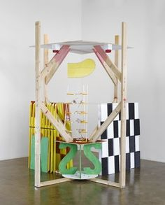 """Richard Tuttle - System 4, Hummingbird, 2011 2 x 4"""", bolts, plastic-coated cable, 1/2"""" painted pine plywood, acrylic artist's color, 4 x 4"""" pine, painted Styrofoam, black gesso, 1/2"""" pine plywood, acrylic, yellow gelatin, staples, nails, 1/2"""" molding strips, 1"""" pine plywood, wall paint, balsa wood with acrylic, armature wire, scotch tape, aluminum wire, molding strips, birch plywood, monofilament, eyebolt 8' x 92"""" x 92"""" © Richard Tuttle, courtesy The Pace Gallery"""