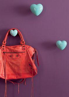 Os cabides verdes em formato de coração na parede roxa conferem feminilidade ao ambiente. Projetado pela arquiteta Andrea Murao