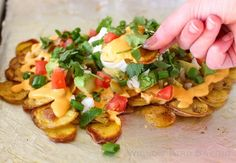 These Over-the-Top Loaded Potato Nachos are perfect for a New Year's Eve party! The recipe includes a tangy, delicious nacho cheese sauce!