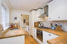 photo of white kitchen with sunken sink tiled splashback tiles wooden worktop worktop wooden floor