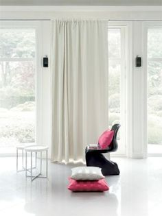 Fibre Naturelle -  Soho Fabric Collection - Long plain white curtains with a moulded black plastic chair, pink and silver scatter cushions and two small white tables
