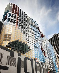 "This university building in Melbourne by Australian architects Lyons is covered in brightly coloured scales. Lyons used a pixellated image of the surrounding buildings to create a map of colour across the exterior. ""The building derives its identity from its surroundings,"", ""It's a chameleon and a mirror"". said Lyons"