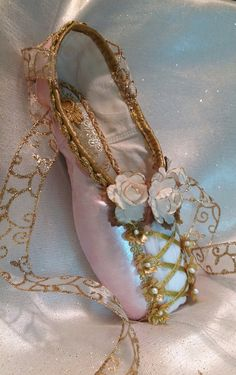 pink and gold decorative pointe shoe designed to mimic the lace up bodice of many traditional ballet costumes