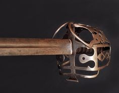 """Scottish basket-hilted Broadsword     Dated: late XVIII century  The sword comes with a straight blade marked 'JJ RUNKEL Solingen'. Runkel was a bladesmith that had his workshop in Solingen circa 1790. This piece is an officer sword, while the actual troops were solely armed with a musket and a bayonet. The sword has an outstanding steel hilt typical of the """"broadsword"""" style. The scabbard (which is lost) must have been in leather and steel."""