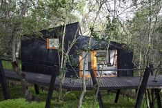 "Sited along a creek near the commune of Curacaví in Chile's Santiago Metropolitan Region, ""Quebrada House,"" which translates to ""ravine house"" in English, is raised on slanted stilts and accessed via a bridge-like walkway with trees rising through its deck.The stilts, or pilotis, helped reduce the co"