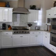 """Dana Nichols  """"The existing cherry cabinets in the kitchen got a coat of glossy white paint as a budget-friendly alternative to replacing them altogether. The new paint also highlights the stainless steel appliances. Blackband added the subway tile Calacatta marble backsplash in a bricklayer pattern. Countertops: Slab Caesarstone in Cinder; cabinet paint color: White (DEW 380), Dunn-Edwards"""""""