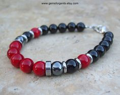 Mens 8mm Beaded Bracelet - Red Coral, Hematite and Black Onyx This bracelet has three types of round stones in the cool color shades of red, gray and black. The focal beads in front of the bracelet are lustrous red coral beads capped by a thick straight edge stainless steel spacer bead