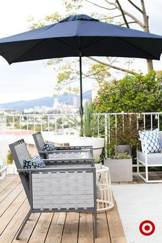 A mixture of cool tones gives an outdoor patio a sophisticated look. The greys, blues and whites of the chairs, umbrella and decor work together to create a space that lends itself to a little R&R.