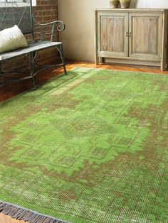 Hand knotted wool in an over dyed aged green with weathered brown details.