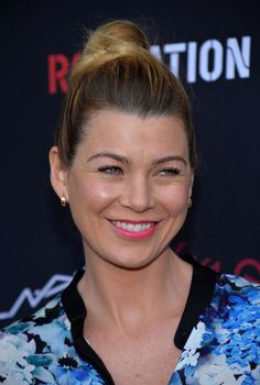 Ellen Pompeo wearing a chic topknot and bright pink lipstick.