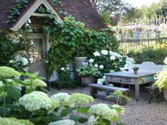 lush climbing vines, white hydrangeas, potted hosta, little peak over door....cozy