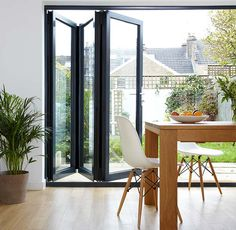 Open blue concertina patio doors, a table and chairs are on the right and a garden outside