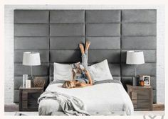 Calming bedroom with big headboard relaxing cool tones grey white neutral lamps magazine female pajamas side tables feet blond hair blanket sheets pillows pillows cases padded silver