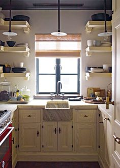 "S.R. Gambrel's West village pied-a-terre kitchen. ""The sides of the stone countertops are chiseled to look like cut marks, and the hardware is slightly exaggerated in scale,"" says Gambrel. The hardware is from a vintage shop in Belgium."