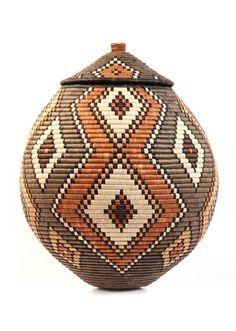 Africa   'Ukhamba' basket from the Zulu people of South Africa   Weavers use strips of naturally waxy palm fronds wrapped around coils of wild grasses.   Some baskets are still used for liquid storage in the rural areas of South Africa. Watertight baskets are readied by rubbing wet cornmeal inside. When liquid is added, the coils swell. Some leaks through, evaporates, and cools the contents.