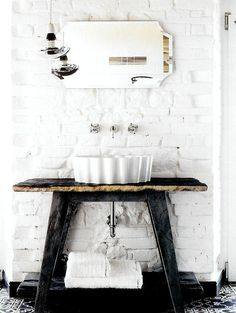 This, I believe, is what they call contrasting textures: a stone vanity top, metal legs, against a white brick wall with what appears to be a giant ceramic quiche dish for a basin!
