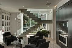 The stair opposite the kitchen is a sculptural element in the space, appearing as stacked blocks zig-zagging their way up and down.    Large windows along the front provide generous natural light to the stairway and family room.