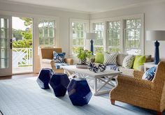 Stylish cottage living room boasts a white trestle coffee table surrounded by a beige sofa topped with neon green and blue anchor pillows facing seagrass roll arm accented with blue striped seat cushions and blue octopus pillows, and three side by side cobalt blue faceted stools all positioned on a light blue rug.