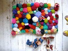 Divertida alfombra de pompones de trapillo de distintos tamaños