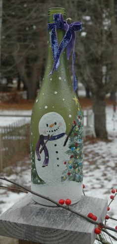 Hand painted wine bottle with fat little snowman - and a Christmas tree.  Tied off with some sparkly ribbon and finished off with a little vintage looking jingle ball.  The whole bottle is sparkly, too, had to see in pics and it comes with lights inside, too!