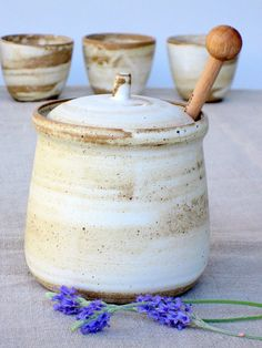 A rustic earthy style jar for storing and serving honey and jam, with a wooden honey dipper. Beautiful to serve at the table for breakfast or dinner and great for storing in the kitchen. To get this soft smooth look, I use dark clay and apply white porcelain slip with a brush. I then glaze it with a matte off white glaze. ✔ I fire all my work to high temperature (1220c/2228f) it produces strong and solid items ✔ All my glazes are food-safe, all my dishes are micro/oven/dishwasher safe ✈ T...