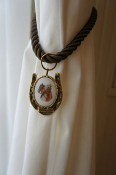 Equestrian curtain tie back using vintage jewelry.