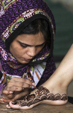 A Pakistani woman paints a customer's feet with henna in preparation for the upcoming Eid al-Fitr festival, in Karachi, Pakistan, Saturday, Aug. 18, 2012. Eid al-Fitr marks the end of the holy month of Ramadan. (AP Photo/Fareed Khan) http://www.davisenterprise.com/media-post/eid-al-fitr/attachment/mideast-israel-palestinians-eid-al-fitr/