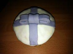Cupcake de vainilla con cobertura de fondant blanco y detalle de lazo en fondant teñido