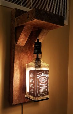 Lit up Jack Daniels bottle on old timber bracket