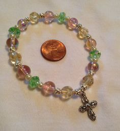 Stretch bracelet with glass beads in Spring colors with silver spacer beads, 3mm glass pearls, and a cross charm $18
