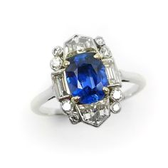 Art Deco sapphire and diamond cluster ring, English c.1925,  the oblong cushion cut sapphire claw set, to a diamond geometric border, collet set with fancy, baguette and round cut stones, stamped serial number 5779