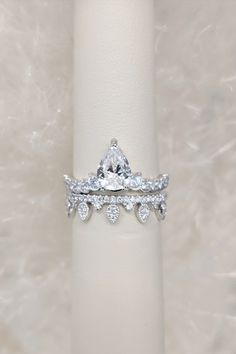 This modern pear shaped diamond engagement ring is paired with a tiara-inspired wedding band. Both are available at Diamonds Direct #pear #pearshape #diamond #engagementring #weddingband #tiara #modern #classique
