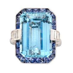 An aquamarine, sapphire and diamond cluster ring, the emerald-cut aquamarine weighing 13.05 carats, set to the centre of a sapphire cluster surround, eight graduated baguette-cut diamonds channel-set to each shoulder, weighing a total of 0.75 carats, all set to a platinum mount and D-section shank. Circa 2000s