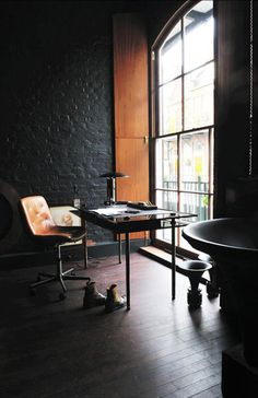leather chair. dark painted brick.