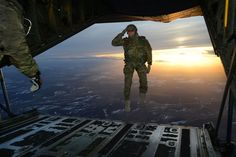 A U.S. Soldier assigned to 1st Battalion, 10th Special Forces Group (Airborne) salutes his fellow Soldiers while jumping out of a C-130 Hercules aircraft over a drop zone in Germany.