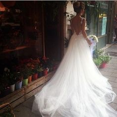 Highly romantic A-line wedding dress with lace straps, open back, lace details, stunning tulle skirt, and cathedral train.