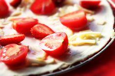 4【トッピング①】 ピザ生地にヨーグルトイチゴソースを一面に敷き詰め、その上にシュッレッドモッツァレラチーズをのせる。 カットしたイチゴとトマトを並べる。
