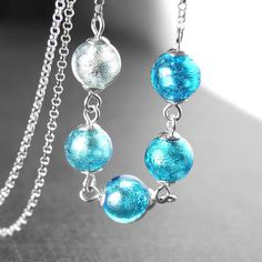 Sky blue beaded Sterling silver chain necklace featuring authentic Sterling silver foil Venetian Murano glass beads. Unique, eye-catching, elegant necklace. More details: - ALL Sterling Silver - elegant chain, wire, bead-cap, and decorative toggle clasp - Stunning, top quality genuine Murano Glass beads (8mm) with splashes of sky/sea blues and shimmering Sterling silver foil which is all covered by clear glass on the outside giving it lots of depth. These special beads have been handcraf...
