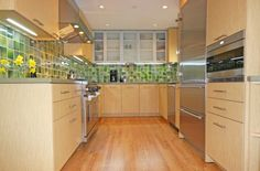 Love the green tiles w/ the blonde wood cabinets